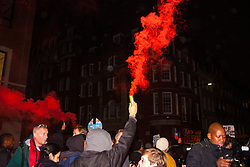 London, November 26th 2014. A vigil for teenager Mike Brown who was shot dead by a policeman in Ferguson, Missouri this year, takes place outside the US embassy in London. Anti-racism and human rights campaigners called the 'emergency' protest following a court verdict that clears Police Officer Darren Wilson of murder. PICTURED: Smoke flares were let off by anti-police-racism protesters as they march through London's exclusive Mayfair.