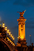 Pont Alexandre III (bridge) across the Seine River. The bridge is the most ornate in the city and features art nouveau lamps, cherubs, nymphs and on the two large gilded sculptures at the end, winged horses. Paris, France.