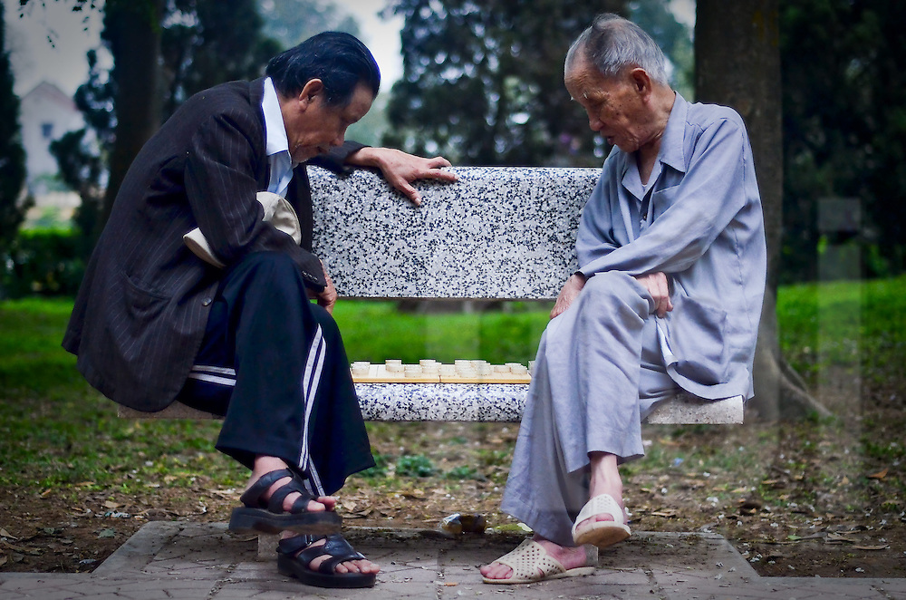 Sat on a public bench, two old vietnamese men play chinese chess. Vietnam, Asia