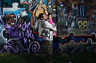 """CLIENT: THE INTERCEPT<br /> <br /> Shaun Young and his daughter Korie, 4 months, in front of a mural in their neighborhood, a few blocks from where Freddie Gray, who died while in police custody a year before, was arrested in Baltimore, Maryland. """"After Freddie, it was like we woke up,"""" says Young, who was arrested himself while confronting an officer who was taking another man into custody. Now Young carries his camera with him everywhere he goes."""