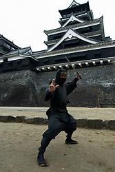 Ninja warrior dressed in black posing outside Kumamoto Castle in Kyushu Japan