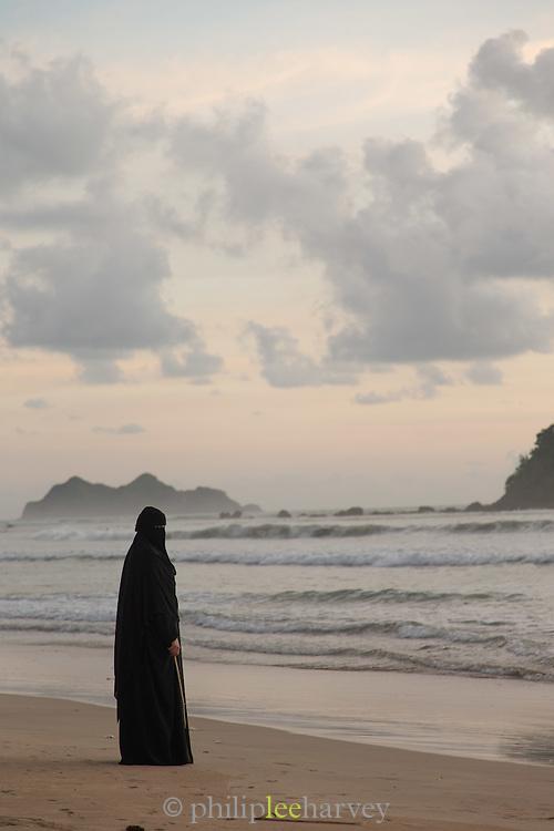 Woman wearing Niqab stood beside the sea holding a stick, Red Island Beach, Red Island, Banyuwangi Regency, East Java, Indonesia, Southeast Asia