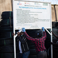 At the IMA and Tearfund Butembo office, a sign for the project to strengthen community response to Ebola is lifted by staff.