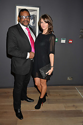 RUBBER RON ELLISTON and CASSANDRA ALICE at a private view of photographs in aid of the Sir Hubert von Herkomer Arts Foundation held at Alon Fine Art, 5-7 Dover Street, London on 8th September 2015.