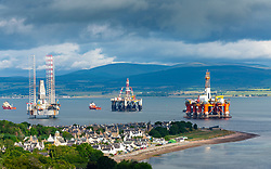 View of Cromarty village and old and gas industry platforms and rigs moored in Nigg Bay on Black Isle on Cromarty Firth, Ross and Cromarty, Scotland, UK