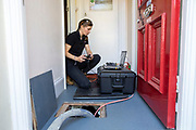 Dayna, controlling the Q-bot under the floor.  Q-bot, underfloor insulation reducing carbon emissions potentially for 12 million households in the UK.   Q-Bot allows under-floor insulation to be installed at a much lower cost and without the disruption of existing methods by using a small robot that goes under the floor instead of having to take the floor up. © Andy Aitchison/ Ashden
