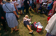 An elderly lady lies oddly on the grass surrounded by crowd of Britons out in Hyde Park to celebrate the 50th anniversary of VE (Victory in Europe) Day on 6th May 1995. As if awoken and surprised at being surrounded by a melee of people, the eccentric woman gives a disapproving stare at a passer-by. In the week near the anniversary date of May 8, 1945, when the World War II Allies formally accepted the unconditional surrender of the armed forces of Germany and peace was announced to tumultuous crowds across European cities, the British still go out of their way to honour those sacrificed and the realisation that peace was once again achieved. Street parties now – as they did in 1945 – played a large part in the country's patriotic well-being.