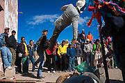 Un hombre lanza un muñeco de tamaño natural relleno de pasto seco, vestido con saco formal, botas vaqueras puntiagudas y sombrero blanco que representa al Judas-mestizo al final de la Semana Santa en Norogachi, México, el 11 de abril de 2009.