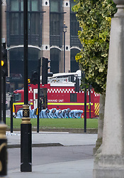 Westminster, London, March 23rd 2017. Police officers in forensic overalls conduct a fingertip search on Parliament Square as investigations continue following Tuesday's terrorist attack on Westminster Bridge and in the grounds of Parliament, in which four people and their attacker were killed with over 40 injured.