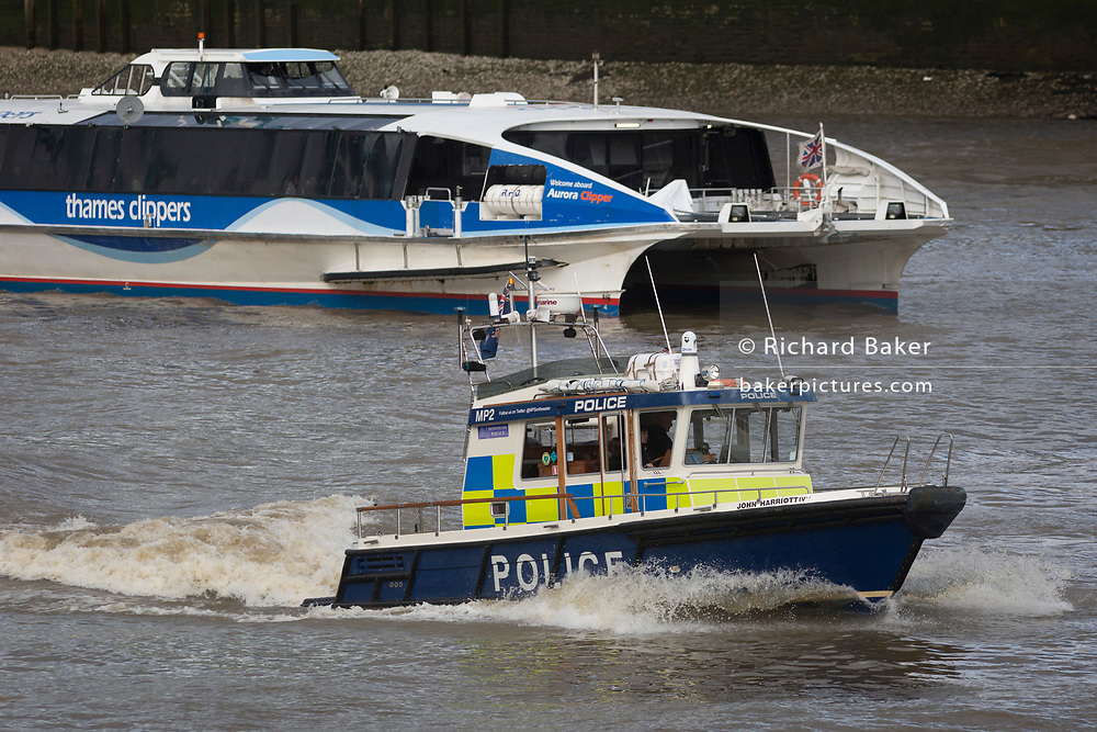 The Metropolitan Police Marine Policing Unit's Thames river police launch, John Harriott IV, passes a Thames Clipper passenger riverboat service on the Thames river, on 17th January 2020, in London, England. John Harriott (1745–1817) was an English seafarer, founder of the 'Marine Police Force'.