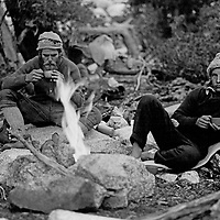 Mountaineers Jay Jensen & Roger Schley (MR) sit by a campfire before climbing in the Palisades region of Sierra Nevada, California (John Muir Wilderness)