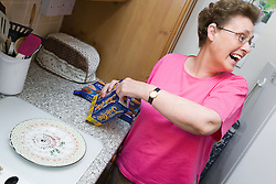 Older woman putting some biscuits out on a plate,