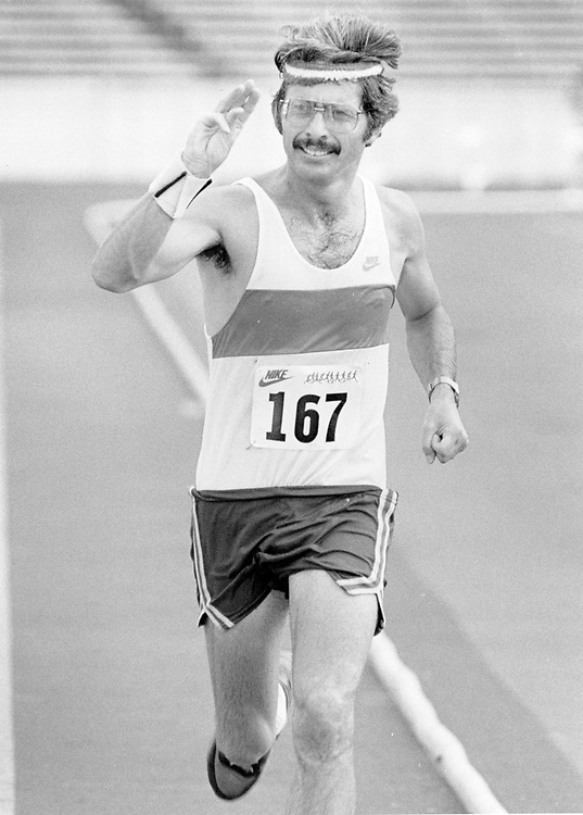 ©1986  Deaf runner making a hand signal on the track during warmups.