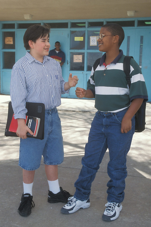 Anglo and African-American teenage boy talk outside of Junior High School.  Model Release.<br /> ©Bob Daemmrich