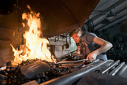 Blacksmith apprentice lightning fire in furnace at workshop, Bavaria, Germany