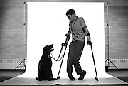 """SHOT 4/19/2007 - University of Denver international studies freshman Patrick Cole, 18, of Littleton with his service dog """"Cooper"""", a five year old male black lab. Cole has cerebral palsy and uses crutches and a wheelchair to get around with some help from """"Cooper"""". Cole received """"Cooper"""" about three and a half years ago from Loving Paws Assistance Dogs and said the dog helps him pick up household items he may have dropped or helps him open doors and such. .(Photo by Marc Piscotty © 2007)"""