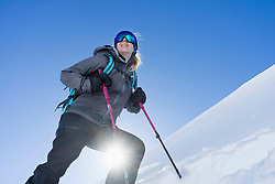 Low angle view of a woman skiing under bright sunlight, Bavaria, Germany, Europe