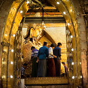 Men apply gold leaf to the body of the Great Image. Mahamuni Buddha Temple (also known as Mahamuni Pagoda) is a highly revered religious site in Mandalay. At its heart is the Mahamuni Buddha image, reputed to be one of only five original likenesses of the Buddha made during his lifetime. It is covered in gold foil donated as tributes by worshippers and pilgrims.