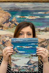 The Bonham's Scottish Sale takes place at Bonham's in Edinburgh on Wednesday 25 April at 1pm. Now in its 19th year it features works by leading Scottish artists as well as a huge range of objects related to Scotland.<br /> <br /> Pictured: Georgina Williams of Bonham's holding the Sale Catalogue in front of Calva Shore, Iona by John Maclauchlin Milner RSA