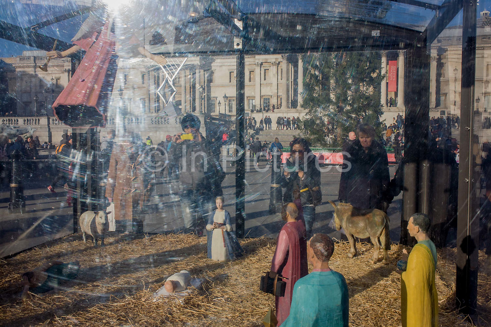 A holy nativity scene titled Christmas Crib by the artist Tomoaki Suzuki with background tourists in London's Trafalgar Square. Encased within a transparent perspex box are the pilgrims who are apparently paying their respects to the infant Jesus in that famous Christian religious event. The new crib was commissioned in 2006 by St Martin-in-the-Fields providing a significant new public art work embodies characters representing different ethnicities - Middle eastern, Caucasian, African and Asian. The 11 painted lime wood carvings are 40% life-size and were a collaboration with fashion designer Jessica Ogden who created timeless silk costumes for each of the characters.
