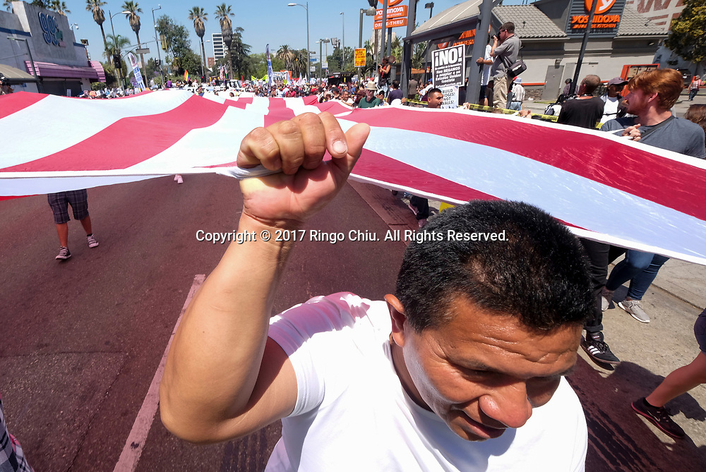 Protesters carry a giant U.S. flag marching toward downtown Los Angeles in the annual May Day March in Los Angeles, May 1, 2017. (Photo by Ringo Chiu/PHOTOFORMULA.com)<br /> <br /> Usage Notes: This content is intended for editorial use only. For other uses, additional clearances may be required.