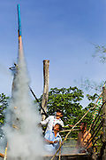 28 JUNE 2014 - DAN SAI, LOEI, THAILAND:  Men launch a rocket from atop a bamboo scaffolding during the Ghost Festival in Dan Sai. The rocket launches are a northern Thai tradition. They're thought to ensure a bountiful rainy season. Phi Ta Khon (also spelled Pee Ta Khon) is the Ghost Festival. Over three days, the town's residents invite protection from Phra U-pakut, the spirit that lives in the Mun River, which runs through Dan Sai. People in the town and surrounding villages wear costumes made of patchwork and ornate masks and are thought be ghosts who were awoken from the dead when Vessantra Jataka (one of the Buddhas) came out of the forest.   PHOTO BY JACK KURTZ