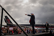 Republican presidential candidate Donald Trump points at cheering supporters as he takes the stage upon arrival for a campaign rally at Lakeland Linder Regional Airport in Lakeland, Florida, October 12, 2016.