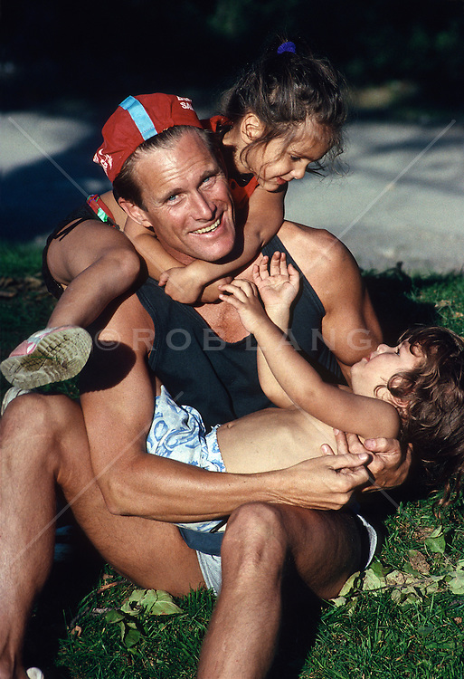Two children climbing on top of good looking man in a park