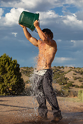shirtless man dumping a bucket of water on himself outdoors