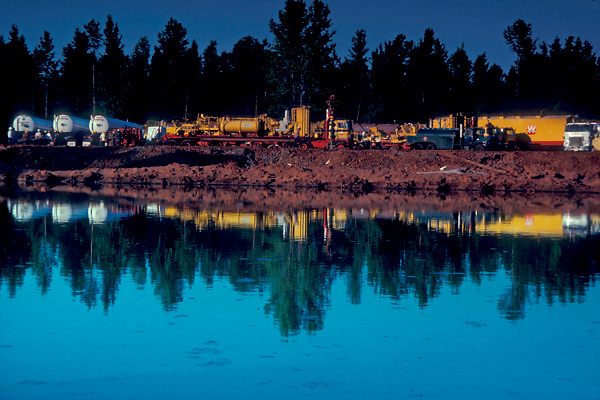 Trucks for heavy transport parked in a line and reflected in a pond