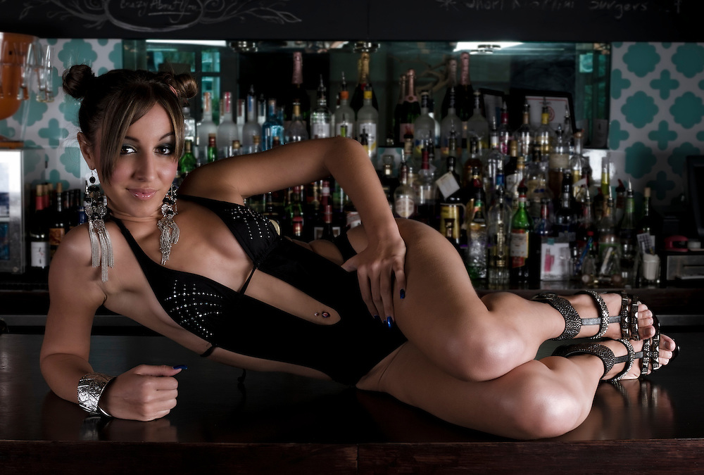 Sensual woman in swimsuit posing in a restaurant bar.