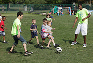 Middletown, New York - Children and counselors chase the ball during a soccer game at Middletown YMCA summer camp on August 20, 2010.