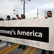 Protesters carriy signs while walking in a protest parade during the Republican National Convention in Tampa, Fla. on Wednesday, August 29, 2012. (AP Photo/Alex Menendez)