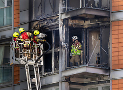 © Licensed to London News Pictures. 07/05/2021. London, UK. Fire fighters inspect the charred remains of apartments at New Providence Wharf in Poplar in east London. 100 fire fighters and 20 crews tackled the blaze at it's peak. Photo credit: Peter Macdiarmid/LNP