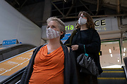 Rail passengers descend an escalator at Victoria Station wearing facial coverings during the Coronavirus pandemic, on 24th August 2020, in London, England.