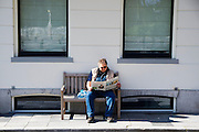 In Utrecht geniet een man op een bank van de lentezon terwijl hij de Volkskrant leest.<br /> <br /> In Utrecht a man is enoying the nice weather on a bench while reading a Dutch newspaper.