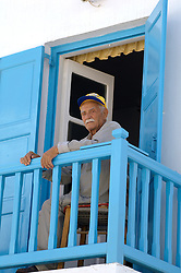 local Greek Man sitting on a colorful balcony in Mykonos, Greece