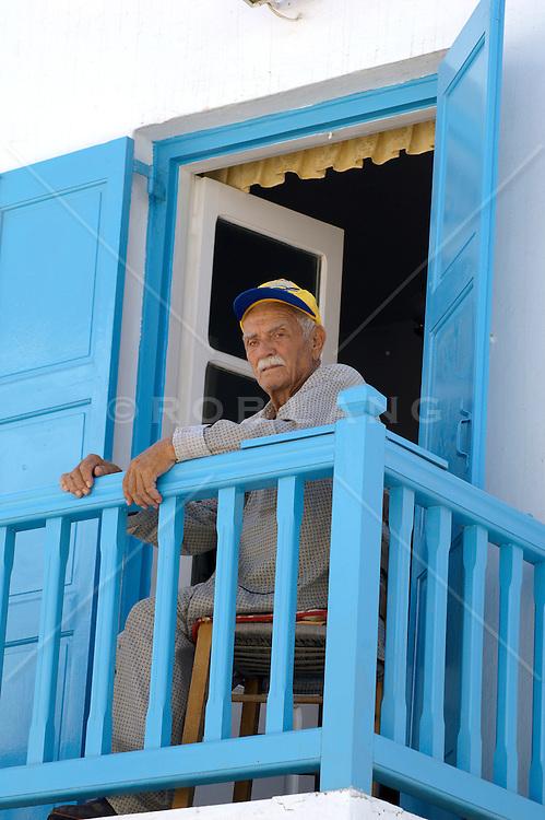local Greek Man sitting on a colorful balcony in Mykonos, Greece