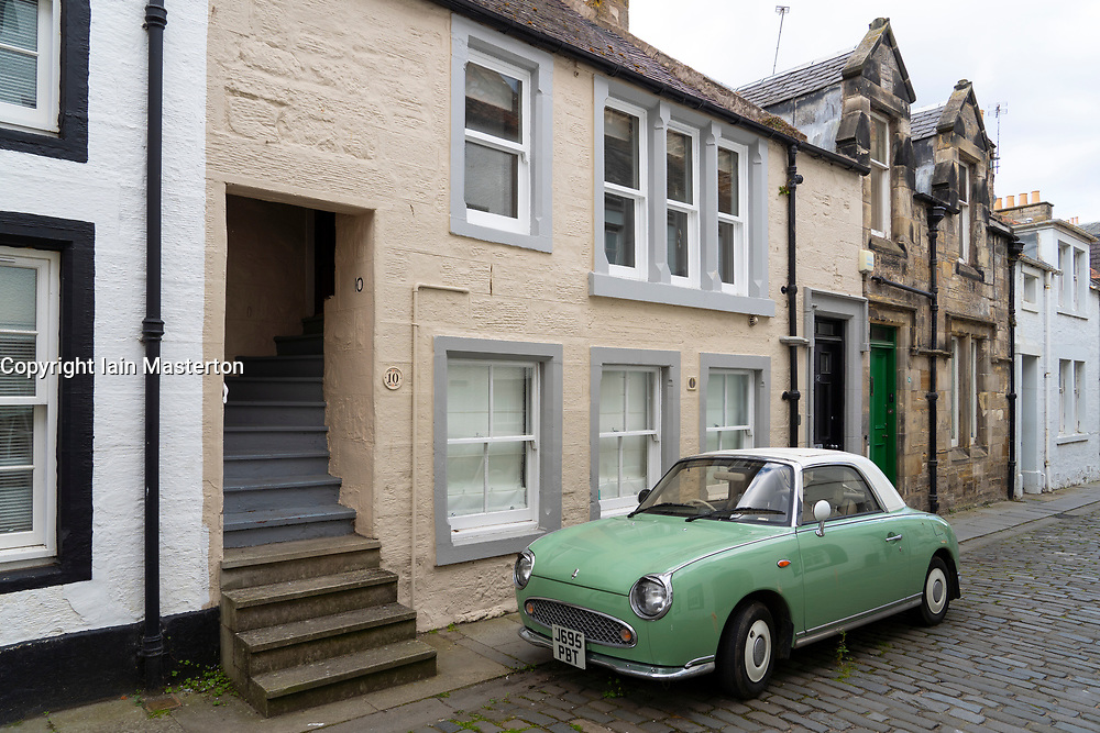View along historic College Street with green car  in central St Andrews, Fife, Scotland, UK