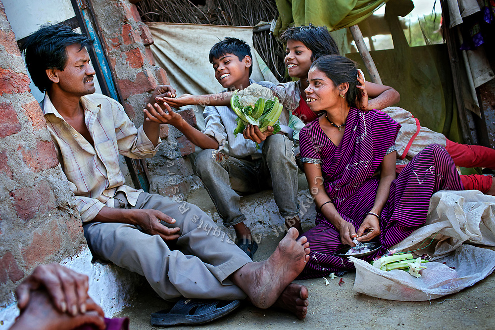 Poonam, 10, sitting next to her brother Ravi, 12, is receiving a coin from their father, Suresh, 43, while in the front yard of their newly built home in Oriya Basti, one of the water-contaminated colonies in Bhopal, central India, near the abandoned Union Carbide (now DOW Chemical) industrial complex, site of the infamous '1984 Gas Disaster'. Sangita, 39, Poonam's mother, is sitting nearby and preparing vegetables for dinner.