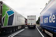 In Utrecht haalt een vrachtwagen tijdens de spits rechts in over de vluchtstrook. Op de invoegstrook en de rijbaan staan vrachtwagens stil in de file.