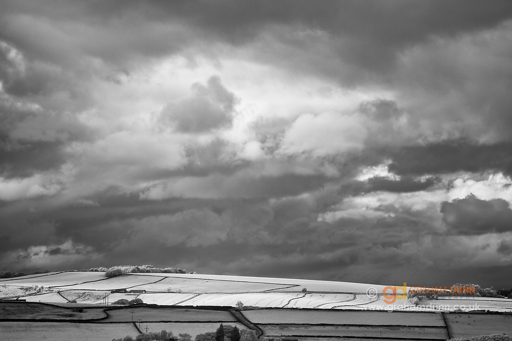 A flash of sunlight picks out Onesmoor, near to High Bradfield, below brooding stormy skies. A moody, infrared landscape scene in the South Yorkshire Peak District, England, UK.