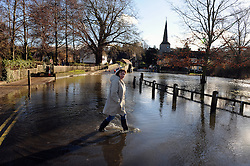 © Licensed to London News Pictures. 19/01/2014. A woman walks through flood water.  The town of Eynsford in Kent flooded where the river Darent has broken it's banks after overnight rain caused river levels to rise. Photo credit :Grant Falvey/LNP