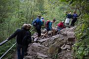 Polish families descend a rocky mountain footpath towards the village of Jaworki, on 21st September 2019, near Szczawnica, Malopolska, Poland.