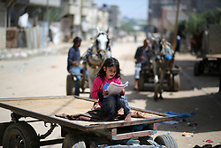 May 22, 2019 - Gaza, gaza strip, Palestine - A Palestinian girle writes outside a house in an impoverished area in Beit Lahia in the northern Gaza Strip on May 22, 2019. (Credit Image: © Majdi Fathi/NurPhoto via ZUMA Press)
