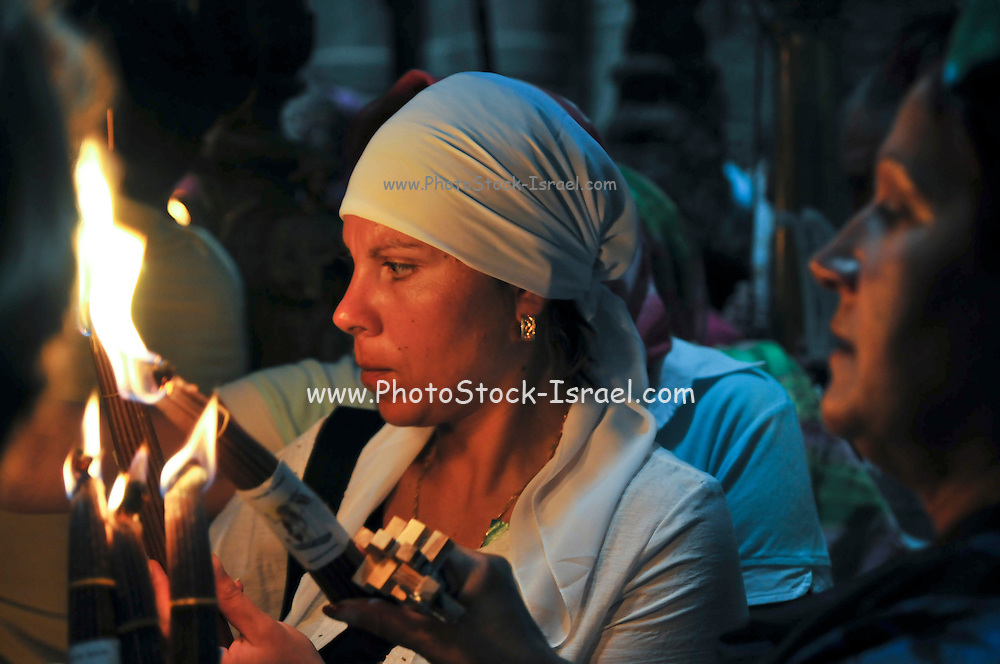 Israel, Jerusalem Old City, the Church of the Holy Sepulchre pilgrims light candles near the Rotunda