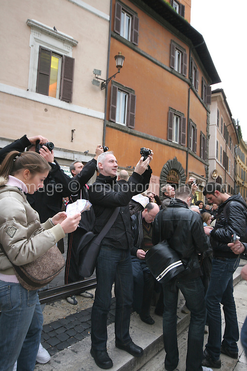 Tourists photographing the Baroque Trevi Fountain in Rome Italy