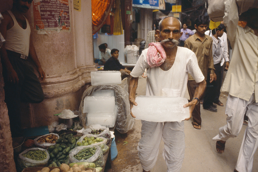 An ice vendor distributing ice to the vegetable shops in the narrow lanes of Old Delhi, July 2003