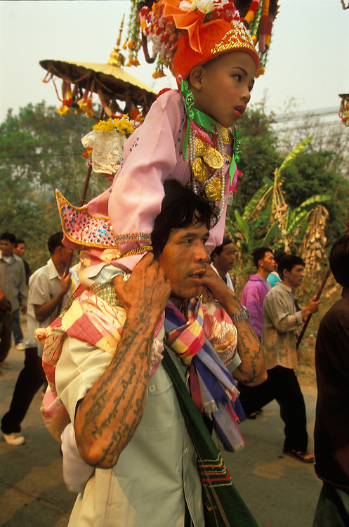 A boy who is dressed up as a prince sits on the shoulders of a man with tattooed arms at a procession during Poy Sang Long, the yearly ordination of novice monks, Mae Hong Son, Thailand.