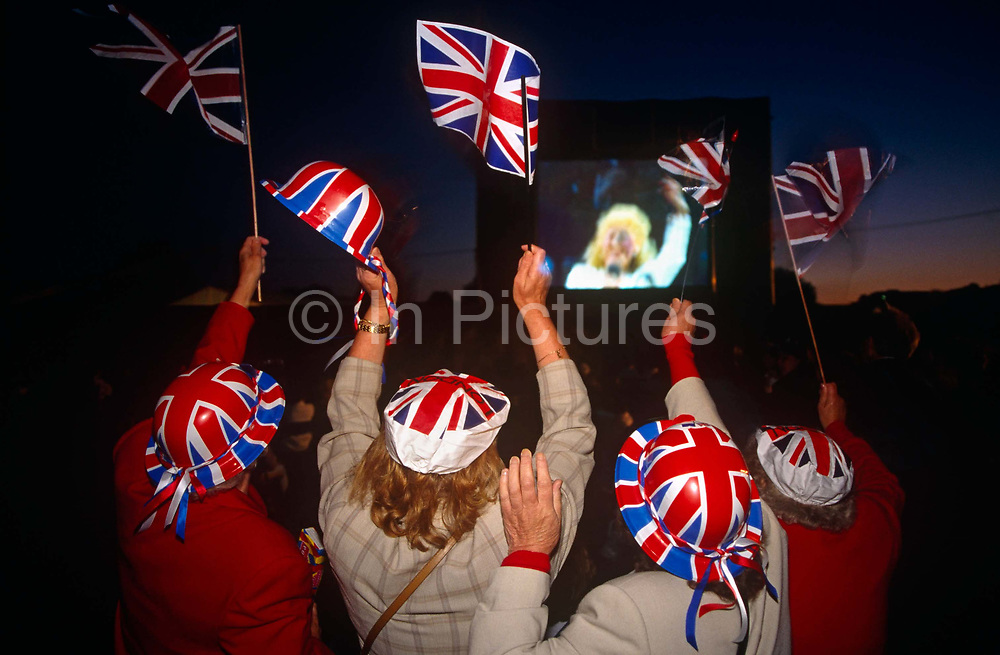 Four ladies are seen from behind wearing Union Jack hats and waving Britain's national flag flags. It is the Queens' Golden Jubilee celebrations in London's Hyde Park and this scene of patriotic fun is common when crowds gather to acknowledge their monarch's long reign over her people. The women's faces are obscured but there is a blurred face of an unknown singer leading a concert of rousing songs - perhaps Rule Britannia - that excites the crowd still in the semi-darkness. It is the end of a long day of marches and appearances of Her Majesty on the balcony of Buckingham Palace, marking her 50th year on the throne.